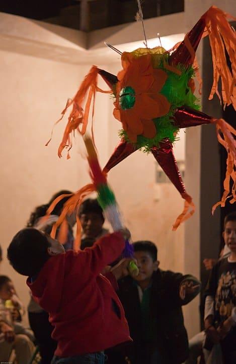 kids celebrating las posadas with a piñata
